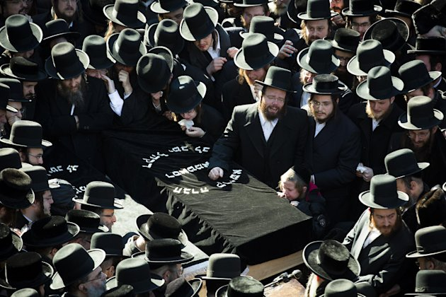 Members of the Satmar Orthodox Jewish community congregate for the funeral of two expectant parents who were killed in a car accident, Sunday, March 3, 2013, in the Brooklyn borough of New York. A dri