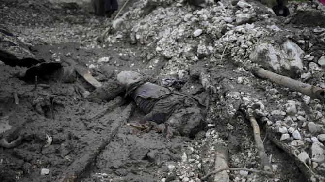 The dead body of a man lies covered in mud and next to the remains of his home, destroyed in a mudslide after Tropical Storm Erika hit the area, in Carries