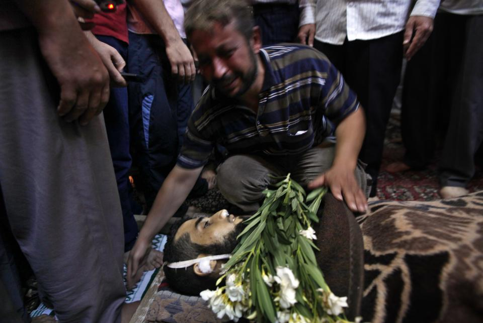 A Syrian relative of 29 year-old Free Syrian Army fighter, Husain Al-Ali, who was killed during clashes in Aleppo, mourns over his body in the mosque before his funeral in the town of Marea on the outskirts of  Aleppo city, Syria, Thursday, Aug. 9, 2012. (AP Photo/ Khalil Hamra)