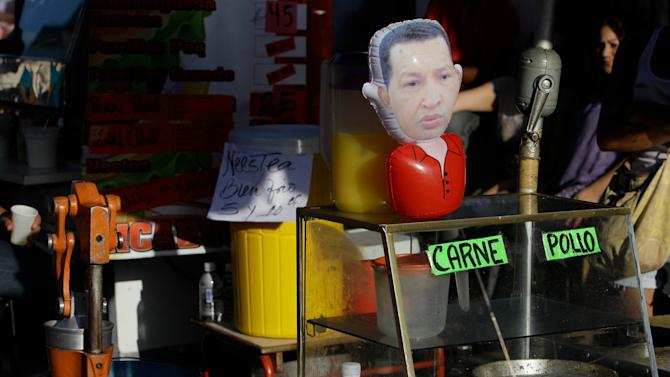 An inflatable doll depicting Venezuela's President Hugo Chavez sits at a street food stall outside the military hospital in Caracas, Venezuela, Monday, Feb. 18, 2013. Chavez returned to Venezuela early Monday after more than two months of treatment in Cuba following cancer surgery, his government said, triggering street celebrations by supporters who welcomed him home while he remained out of sight at Caracas' military hospital. (AP Photo/Fernando Llano)