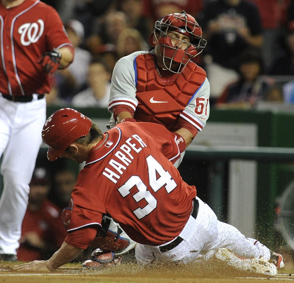 Washington Nationals'  baserunner Bryce Harper steals home as Philadelphia Phillies catcher Carlos Ruiz applies a late tag during first inning of their baseball game at Nationals Park, Sunday, May 6, 2012, in Washington. Harper was on third base went he scored to give the Nationals a 1-0 lead. (AP Photo/Richard Lipski)