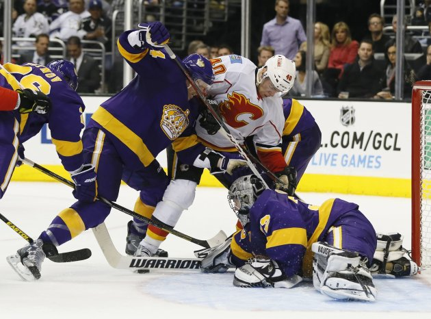 Calgary Flames' Alex Tanguay attempts to score as Los Angeles Kings' Colin Fraser and goaltender Jonathan Quick defend during the third period of their NHL hockey game in Los Angeles