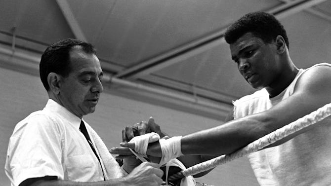 File - In this May 10, 1966, file photo, World Heavyweight Boxing champion Muhammad Ali, right, looks on as his hands are taped by trainer Angelo Dundee, left, before sparing with Jimmy Ellis during a training session at the Territorial Army Centre in White City, London, England. Dundee, the trainer who helped groom Ali and Sugar Ray Leonard into world champions and became one of boxing's most recognizable figures, died Wednesday, Feb. 1, 2012. He was 90. (AP Photo/Kemp, File)