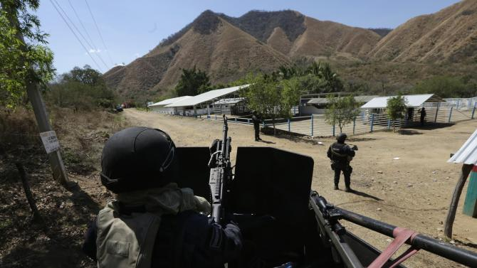 """Federal police stand guard outside one of the ranches where Servando """"La Tuta"""" Gomez lived, during a media tour near the town of Uruapan in Michoacan state"""