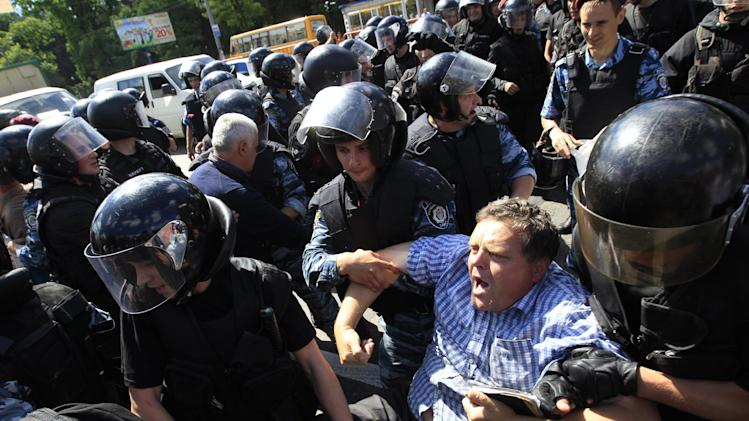 Riot police stop Orthodox protesters who are trying to stop Ukraine's first gay pride demonstration in Kiev, Ukraine, Saturday, May 25, 2013. About a hundred gay and lesbian Ukrainians and those from other countries took part in the gay pride rally, protected by hundreds of riot police. Antipathy toward homosexuals remains strong in Ukraine. (AP Photo/Sergei Chuzavkov)