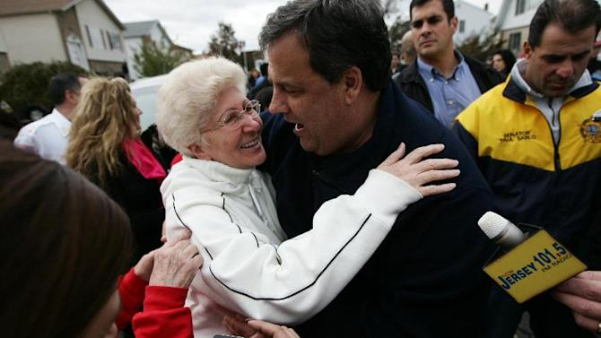 """Angela Cimillo, of Moonachie, N.J., whose home was damaged during Superstorm Sandy, left, hugs New Jersey Gov. Christie Thursday, Nov. 1, 2012, as the governor toured the flood-ravaged area. The flooding of Moonachie, Little Ferry and Carlstadt, three communities sandwiched between Teterboro Airport, MetLife Stadium and the Hackensack River, was caused by six dirt berms that broke from the pressure of a tidal surge, Christie said. More than 1.7 million customers in New Jersey remain without power _ down from over 2.7 million at the height of the outages. """"Take care of us,"""" Cimillo told Christie. (AP Photo/The Record of Bergen County, Kevin R. Wexler, Pool)"""