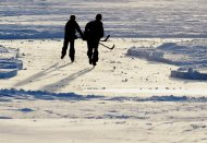 Kids chase a puck on Lake Banook in Dartmouth, N.S. on Sunday, Jan. 5, 2014. THE CANADIAN PRESS/Andrew Vaughan