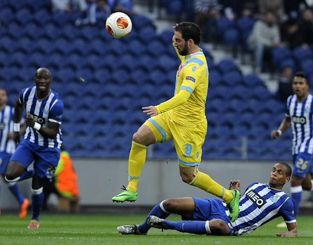 Napoli's Gonzalo Higuain, from Argentina, drives the ball past FC Porto's Fernando Reges, on the pitch, from Brazil during their Europa League round of 16, first leg soccer match at the Dragao
