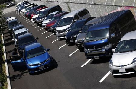 A staff checks a car parked outside of Toyota Motor Corp's showroom in Tokyo