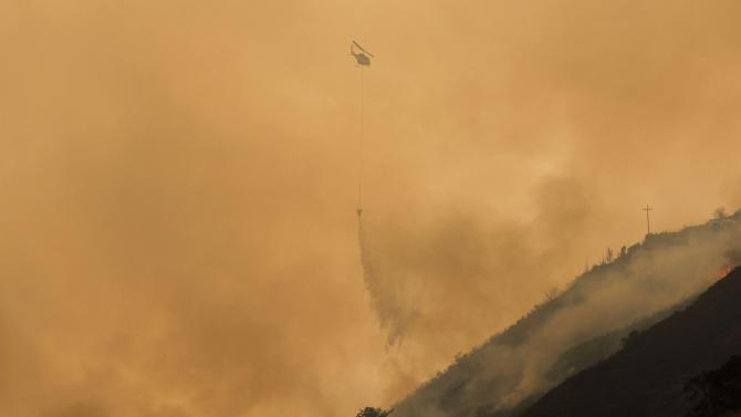A helicopter drops ocean water on a wildfire burning on Pfeiffer Ridge in Big Sur, California