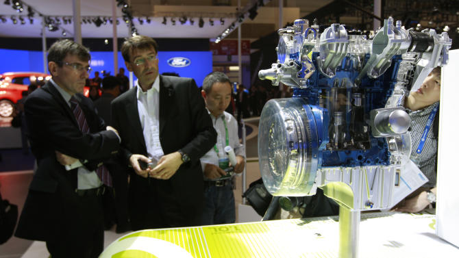 Visitors look at Ford's EcoBoost 1.0 liter engine at the Beijing International Auto Exhibition in Beijing, China, Monday, April 23, 2012.  (AP Photo/ Vincent Thian)