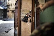 Free Syrian Army fighters are reflected in a mirror they use to see a Syrian Army post only 50 meters away as they man a position in the Old City of Aleppo. Fighting raged in Syria's two biggest cities on Sunday as UN-Arab League envoy Lakhdar Brahimi ended his first visit to the country on a peace mission a rebel commander said was doomed to fail