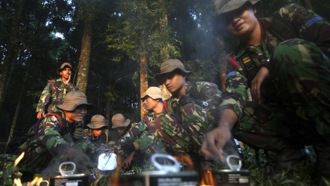 Indonesian soldiers mobilized for search of a missing Russian plane cook food at Taman Nasional Halimun Salak in Sukabumi, West Java, Indonesia, Thursday morning, May 10, 2012. Search and rescue teams were scouring the slopes of a dormant volcano in western Indonesia early Thursday for signs of a new Russian-made passenger plane that dropped off the radar while on a demonstration flight Wednesday. (AP Photo/Achmad Ibrahim)