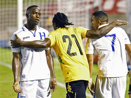 Jamaica's Anderson reacts at Honduras' Figueroa and Izaguirre during their 2014 World Cup qualifying soccer match in Kingston