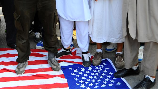 In this photo taken Wednesday, Sept. 12, 2012, Islamic Tunisian protesters step on a U.S. flag during a protest outside the outside the U.S. embassy in Tunis, as part of widespread anger across the Muslim world about a film ridiculing Islam's Prophet Muhammad. Leaked conversations in which alcohol bans and the imposition of religious law were mentioned have raised fears Tunisia's new government may not be moderate at all, especially in the context of mob attacks on the U.S. Embassy that coincided with the American ambassador's killing in neighboring Libya. (AP Photo/Hassene Dridi)