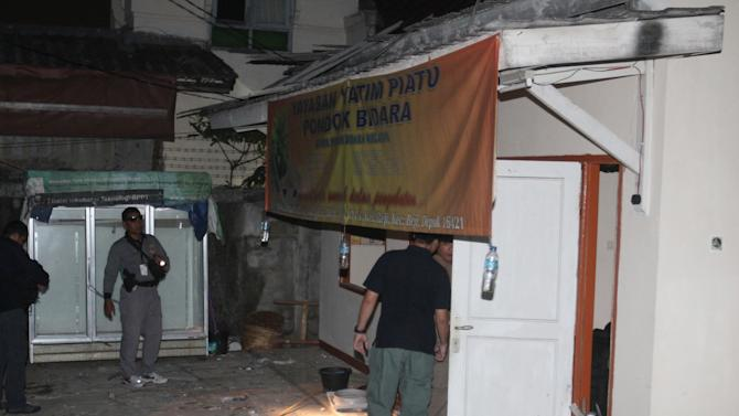 In this late Saturday, Sept. 8, 2012 photo, plain-clothed police officers examine a house where an explosion went off in Depok, West Java, Indonesia. A bomb being prepared for a terrorist attack has exploded at the house injuring five people, police said. (AP Photo)