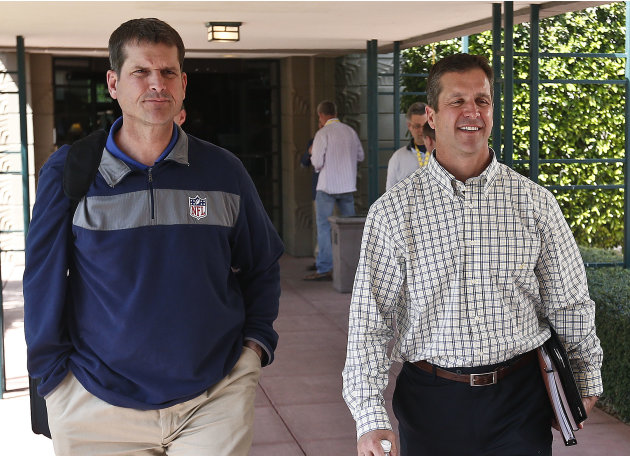 San Francisco 49ers coach Jim Harbaugh, left, walks with his brother John Harbaugh, coach of the Baltimore Ravens, at the NFL football annual meetings Tuesday, March 19, 2013, in Phoenix. (AP Photo/Ro