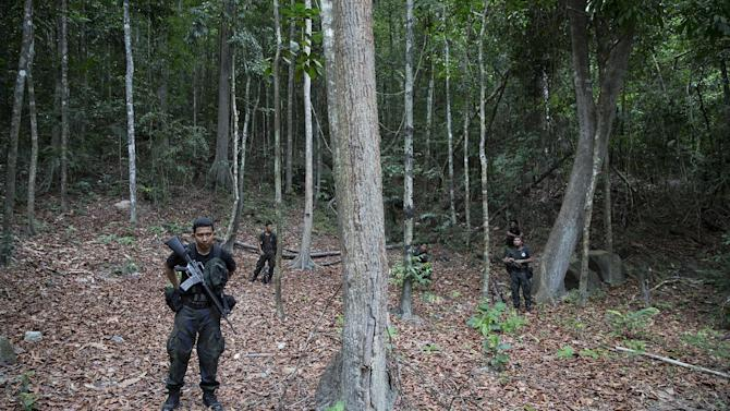 Policemen take position near the abandoned human trafficking camp in the jungle close the Thailand border at Bukit Wang Burma in northern Malaysia