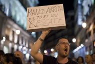 A protester against Spain's bailout holds up a sign in Madrid