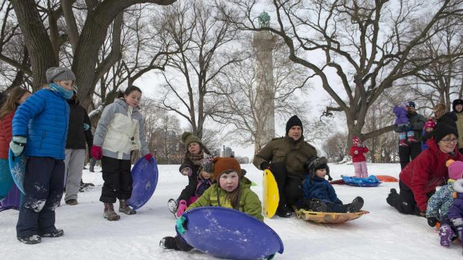 Family members play in Fort Greene Park in Brooklyn after a snow storm in New York