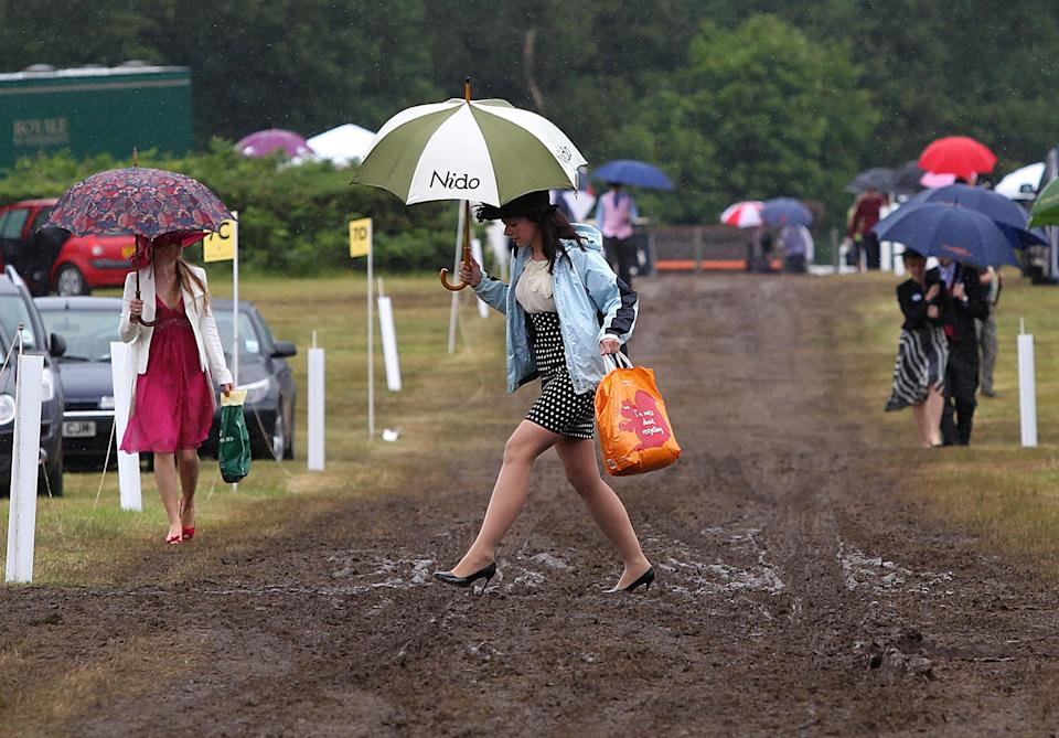 Racegoers make their way through a muddy car park, as rain continues to fall on the fourth day of the annual Royal Ascot horse race meeting at Ascot,. England, Friday June 17, 2011.(AP Photo/David Davies-pa)  UNITED KINGDOM OUT: NO SALES: NO ARCHIVE: