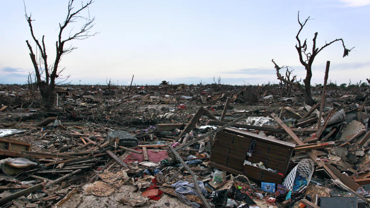 The rubble of a destroyed neighborhood is strewn about a neighborhood in Moore, Okla., Tuesday, May 21, 2013.   Many homes were stripped to their foundations Monday by a tornado which moved through  the area.  (AP Photo/Brennan Linsley)