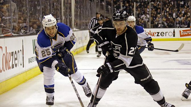 Los Angeles Kings defenseman Alec Martinez (27) moves the puck, chased by St. Louis Blues right winger Chris Stewart (25) in the third period of Game 4 of the NHL Western Conference Stanley Cup hockey playoff series in Los Angeles, Saturday, May 4, 2013. The Kings won, 4-3. (AP Photo/Reed Saxon)