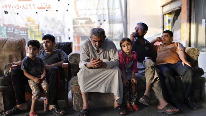 File photo of An Iraqi Shi'ite man using his phone as he sits at an outdoor cafe in Sadr City in Baghdad