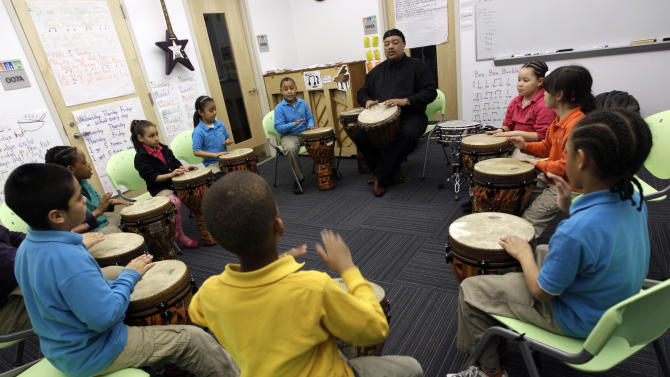 In this April 13, 2011 photo, percussion teacher Don Eaton, center, aka Baba Don, conducts drumming class at the Mott Haven Academy Charter School, in the Bronx borough of New York. The school is trying to chart a course for others nationwide with a program designed to give foster children better odds at a good future. The school is sponsored by a citywide private child welfare agency, the New York Foundling. Foundling Executive Director Bill Baccaglini says the Foundling's Bronx Community Services shares the building with the school. Thus, there are always more than 200 counselors on call to help students individually. (AP Photo/Mary Altaffer)