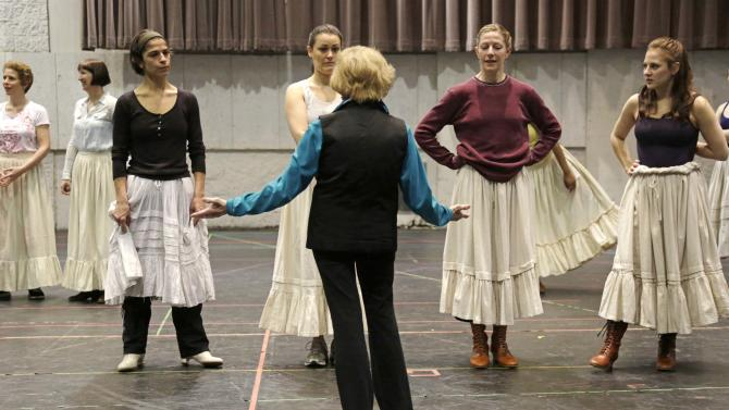 "In this April 26, 2013 photo, choreographer Gemze de Lappe center, directs cast members during a rehearsal of Rodgers and Hammerstein's ""Oklahoma!"" at the Lyric Opera of Chicago. De Lappe first danced in ""Oklahoma!"" in 1943 as a member of the Broadway hit's first national touring company and now 70 years later at age 91 she's choreographing a production of the musical at the Lyric. (AP Photo/M. Spencer Green)"