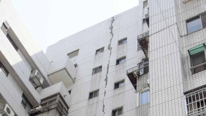 A large crack lines the entire exterior wall of a building in Taichung, central Taiwan, Wednesday, March 27, 2013,  following a strong earthquake early in the day. The 6.1 quake struck central Taiwan on Wednesday, killing at least one person and injuring 19 as it damaged buildings on the quake-prone island. (AP Photo) TAIWAN OUT