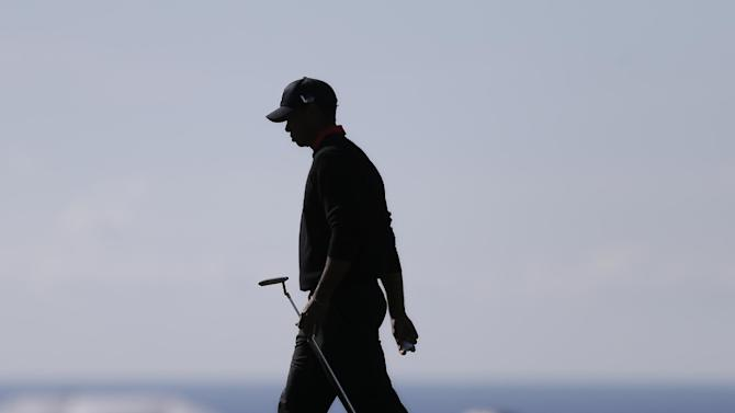 Tiger Woods is silhouetted as he walks across the 14th green during the final round in the Farmers Insurance Open golf tournament Monday, Jan. 28, 2013, in San Diego. (AP Photo/Lenny Ignelzi)