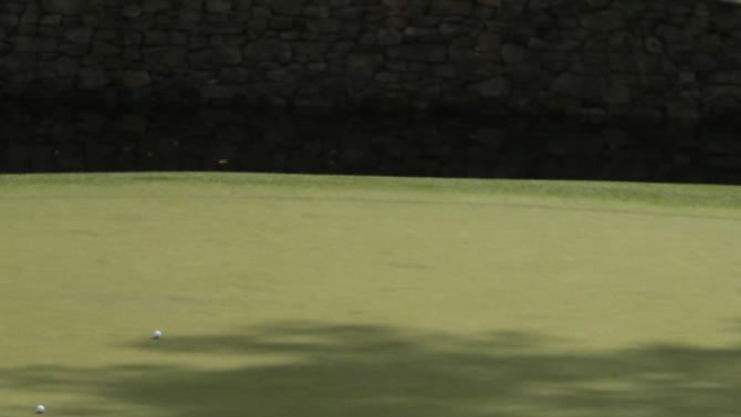 Tiger Woods, right, points to the hole on the 11th green while talking to amateur Guan Tianlang, of China, during a practice round for the Masters golf tournament Monday, April 8, 2013, in Augusta, Ga. (AP Photo/Charlie Riedel)