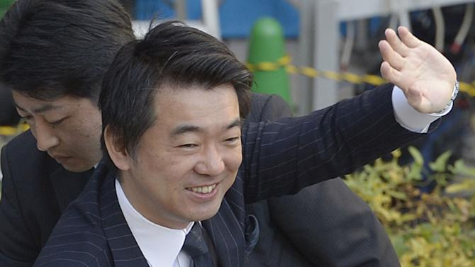 """In this Dec. 4, 2012 photo, Japan Restoration Party acting leader Toru Hashimoto waves at his party supporters during his parliamentary elections campaign in Osaka, western Japan. The buzz over Japan's parliamentary elections this Sunday, Dec. 16, has been all about """"the third force"""" - a clear sign of the prevailing disenchantment over both the party that ruled for decades after World War II and the rival party that took over in 2009. The new party with the most momentum, and one that could be part of the coalition government, is the Japan Restoration Party, led by Tokyo Gov. Shintaro Ishihara and Osaka Mayor Hashimoto, pushing for a more assertive Japan and capable of flexing its military muscle in territorial disputes with China. (AP Photo/Kyodo News) JAPAN OUT, MANDATORY CREDIT, NO LICENSING IN CHINA, FRANCE, HONG KONG, JAPAN AND SOUTH KOREA"""