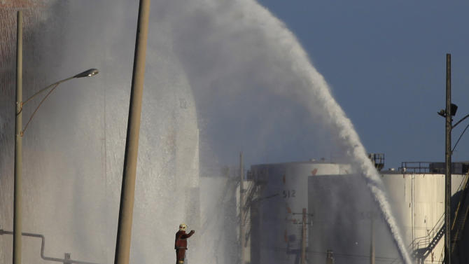 Firefighters douse a fuel tank at the Amuay refinery near Punto Fijo, Venezuela,Tuesday, Aug. 28, 2012. Officials said Tuesday that all fires have been extinguished at Venezuela's biggest oil refinery after raging for more than three days following a deadly explosion early Saturday. (AP Photo/Ariana Cubillos)
