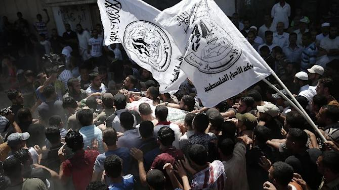 Palestinian Hamas supporters carry the body of one of three Hamas commanders killed in an Israeli military strike, during their funeral in Rafah, Gaza on August 21, 2014
