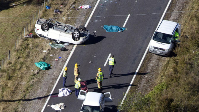 FILE - In this May 12, 2012 file photo, police and fire crew members examine the scene of a minivan crash near Turangi, New Zealand. Three Boston University students who were killed last year in New Zealand when their minivan rolled might have survived if they were wearing seatbelts, police said Wednesday, June 12, 2013. Constable Tina Mitchell-Ellis told a coroner's court that the three who died and a fourth who suffered brain trauma in last May's accident weren't wearing belts and were thrown from the van. She said four others who were wearing belts suffered only minor injuries. (AP Photo/NZ Herald, John Cowpland, File) NEW ZEALAND OUT, AUSTRALIA OUT