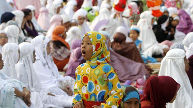 An Indonesian girl yawns as she attends Eid al-Fitr prayers that marks the end of the holy fasting month of Ramadan at Sunda Kelapa port in Jakarta, Indonesia, Sunday, Aug. 19, 2012. (AP Photo/Tatan Syuflana)