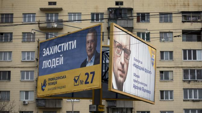 Pre-election posters with portraits of Ukraine's Prime Minister Yatseniuk, leader of political party People's Front, and former Ukrainian Defence Minister Hrytsenko, leader of political party Civil Position are seen at the street in Kiev