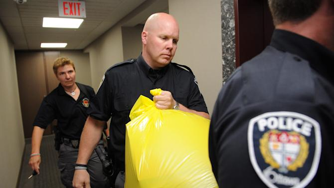 A police officer removes a package from the Conservative Party headquarters in Ottawa, Ontario, on Tuesday, May 29, 2012. A severed human foot was mailed to the headquarters of Canada's Conservative party and another body part was discovered when police intercepted a second suspicious package, police said Tuesday. (AP Photo/The Canadian Press, Sean Kilpatrick)