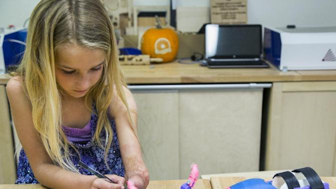 Faith Lennox, 7, adjust her newly 3-D printed hand at the Build it Workspace in Los Alamitos, Calif., on Tuesday, March 31, 2015.  Build It Workspace is a 3-D printer studio that teaches people to use high-tech printers and provides access to them for projects.  Faith's new hand is the result of an emerging technology that is revolutionizing prosthetics, said Build It's Mark Lengsfeld, especially for children like Faith, who quickly outgrow expensive prosthetic limbs and have trouble even using them because of their size and weight. (AP Photo/Damian Dovarganes)