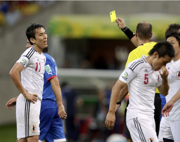 Japan's Makoto Hasebe receives a yellow card from referee Diego Abal of Argentina  after he conceded a penalty to Italy during their Confederations Cup Group A soccer match at the Arena Pernambuco in