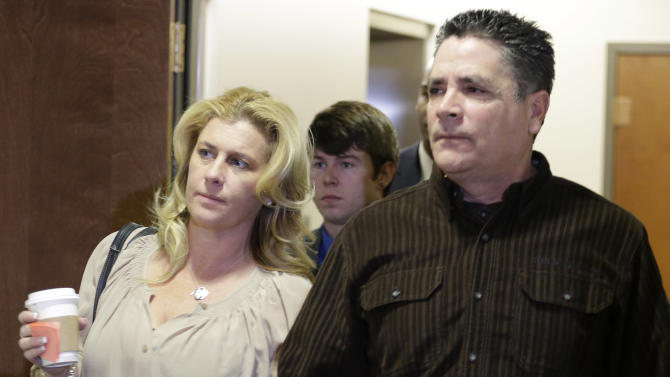 "Steve Hernandez, right, the father of Rebecca Wingos who was killed in the Aurora theater, holds hands with an unidentified woman as they arrive for a court proceeding for Aurora theater shooting suspect James Holmes at the courthouse in Centennial, Colo., on Friday, Jan. 11,  2013. Hernandez yelled out ""Rot in Hell Holmes"" in court at the end of Friday's proceedings. (AP Photo/Ed Andrieski)"