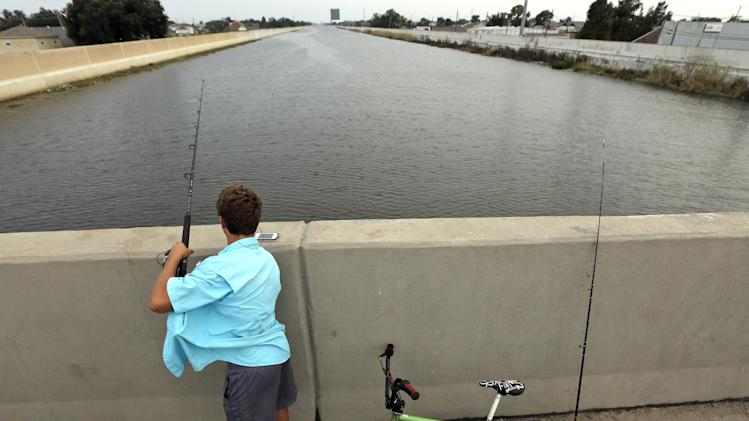 Dylan Lacoste, 14, fishes from the 17th Street Canal bridge Monday, Aug. 27, 2012, in New Orleans. Seven years ago this week Hurricane Katrina hit New Orleans. Tropical Storm Isaac is churning it's way across the Gulf of Mexico and could make landfall near New Orleans later this week. (AP Photo/David J. Phillip)