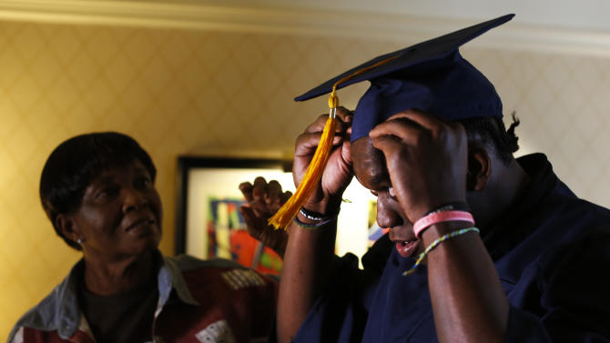 IMAGE DISTRIBUTED FOR NIKE - Ziggy Ansah, defensive end from Brigham Young University, puts on his graduation cap and gown alongside his mother in the hours before the 2013 NFL Draft begins, Thursday, April 25, 2013, in New York. (John Minchillo/AP Images for NIKE)