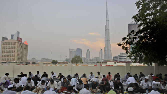 With World's tallest tower, Burj Khalifa in the background, Muslim's break their fast at a mosque in Dubai, United Arab Emirates, Sunday Aug. 7, 2011. Mohammed al-Qubaisi, Dubai's top Muslim cleric, said Sunday that Burj Khalifa residents living above the 80th floor should wait two additional minutes to break their dawn-to-dusk fast while those above the 150th floor must wait three extra minutes because they will be able to see the sun longer than those on the ground. (AP Photo/Kamran Jebreili)