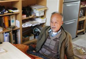 Horiuchi, an evacuee from the town of Tomioka, speaks to Reuters in his temporary housing unit, in Iwaki