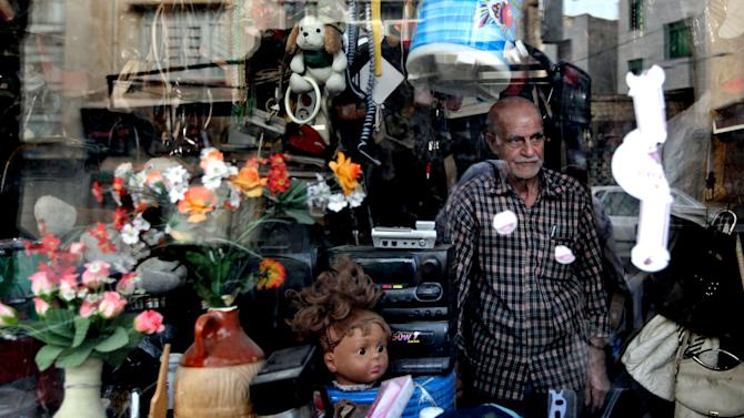 In this Tuesday, May 28, 2013 photo, an Iranian elderly man, stands at his shop, selling second hand items, in downtown Tehran, Iran. On the roughneck streets in south Tehran, paramilitary volunteers look to the most hard-line presidential candidate as the best defender of the Islamic system. On the other end of Tehran's social ladder, a university professor plans to snub next week's election. In between is a mix of splintered views, apathy and indecision based on dozens of AP interviews suggesting a still wide open race. (AP Photo/Vahid Salemi)