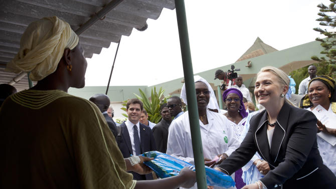 Secretary of State Hillary Rodham Clinton gives a mosquito net for malaria prevention to a local woman during a tour of the Philippe Senghor Health Center in Dakar, Senegal, Wednesday, Aug. 1, 2012. (AP Photo/Jacquelyn Martin, Pool)