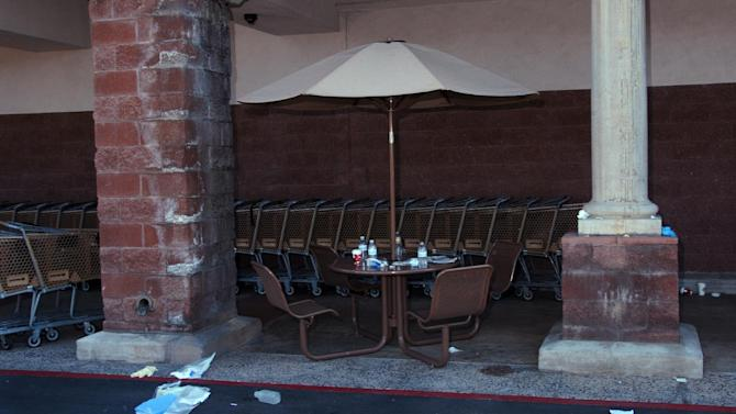 In this image released by the Pima County Sheriff's department, medical gloves and other debris are seen near a lunch table outside of a Safeway grocery store, in the aftermath of the Tucson shooting rampage that killed six people and wounded former U.S. Rep. Gabrielle Giffords and 12 others in January 2011.  Authorities released more than 300 photos on Tuesday, May 21, 2013, made by investigators during their investigation in the parking lot of the shopping center where the shooting took place.  (AP Photo/Pima County Sheriff)